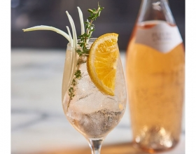 Cocktail in a wine glass with an orange slice and a sprig of thyme